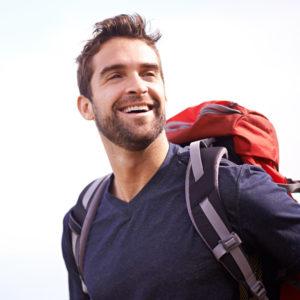 man hiking and smiling